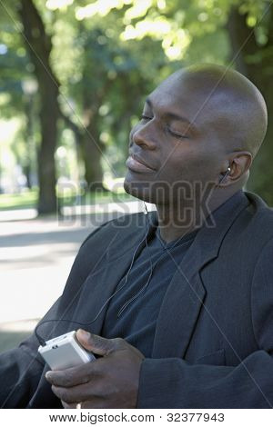 African man listening to mp.3 player in park