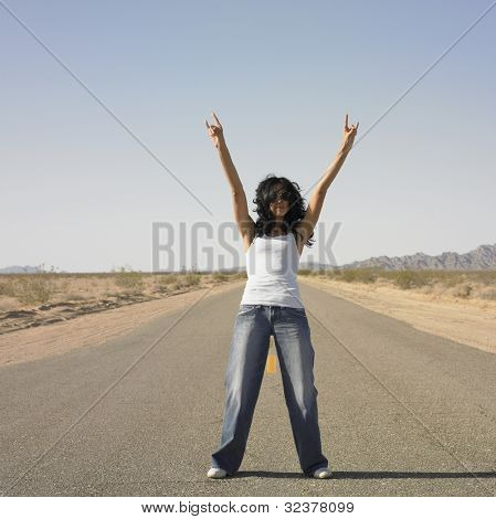 Woman standing in middle of deserted road with arms raised