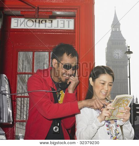 Asian couple using public telephone box and map in London