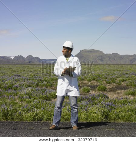 Man with hard hat and clipboard standing on side of deserted road