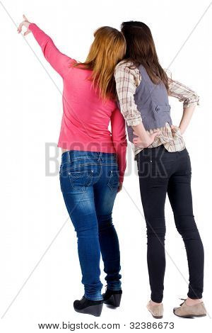 Back view of two young woman (brunette and blonde) pointing at wall . Rear view people collection.  backside view of person. beautiful girl friends  showing .   Isolated over white background.
