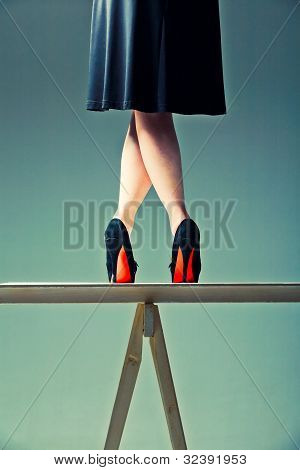 Slender Female Legs Crossed On The Table