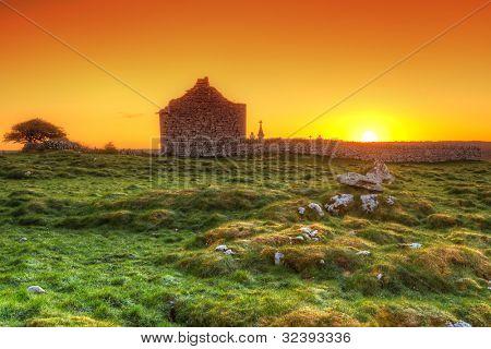 Ruins of old Irish chapel in Burren at sunrise