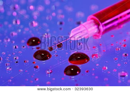 Syringe needle with fluid (blood) drops on droplets water background, macro view
