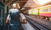 Young Asian Man Traveler With Backpack In The Railway, Backpack And Hat At The Train Station With A  poster