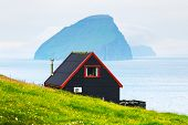 Black house on famous faroese Witches Finger Trail and Koltur island on background. Sandavagur villa poster