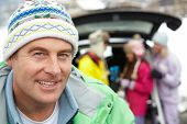 stock photo of portrait middle-aged man  - Father Smiling At Camera Whilst Family Load Skis In Boot Of Car - JPG