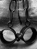 stock photo of shackles  - Black and white image of a pair of shackles shot in Berncastle Germany - JPG