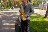 Man Plays On Saxophone In The Park. Street Musician With Sax Performs Music For Charity. Public Solo poster