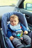 Baby Car Seat For Safety. Cute Baby Boy In Safety Car Seat With Safety Belt Locked Protection. Prote poster