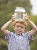 stock photo of glass frog  - Young boy looking at frog in glass jar outdoors - JPG