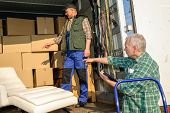 stock photo of movers  - Two male movers unload furniture and boxes  from moving truck - JPG