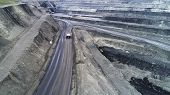 Coal Mine, Aerial View. A Gravel Road Located On A Rocky Ledge. Heavy Mining Dump Truck Takes Overbu poster