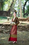 Young Asian Women In Traditional Dress Standing On Old Wall Look At Camera With Bow Of Lotus In Hand poster