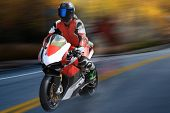 Motorcycle Racer In Helmet And Gear At High Speed Racing On The Race Track poster