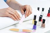 Woman Using Nail File And Create Perfect Nails Shape. Colorful Nail Polish Bottles On Table. Grindin poster