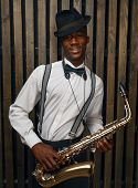 Black smiling jazz musician poses with saxophone poster
