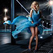 Постер, плакат: женщина смотрит как Мэрилин Монро стоя с платьем на ветру