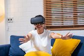 Young Asian  Woman Touching Air During The Vr Reality Experience Wearing Virtual Reality Goggles .fu poster