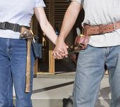 stock photo of track home  - Couple holding hands and wearing tool belts - JPG