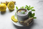 Glass Cup Of Ginger Tea With Lemons And Mint Leaves On Light Background. Ginger Tea, Drink Ingredien poster