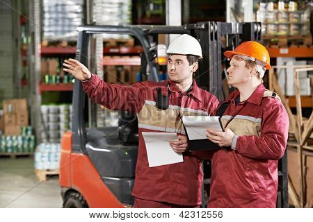 young smiling warehouse workers in uniform in front of forklift stacker loader