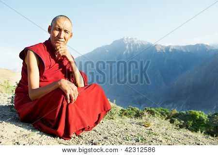 Two Indian tibetan old monks lama in red color clothing sitting in front of mountains