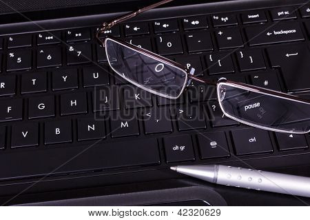 Glasses And Pen On A Computer Keyboard