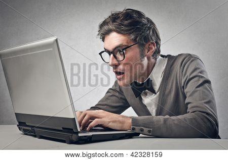 astonished boy working on laptop