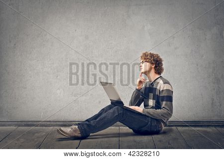 young man with laptop sitting on floor