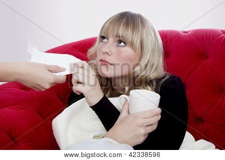 Young Beautiful Blond And Red Haired Girls Has A Cold And Get A Hankie On Red Sofa In Front Of Grey