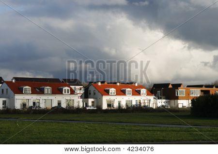 Sol en casas bajo un cielo de trueno