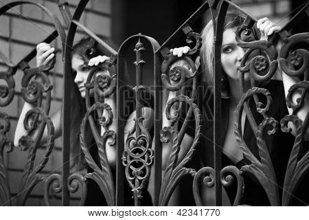 Two sad young women clinging on iron fence