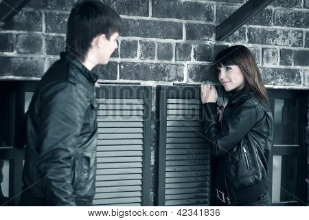 Young couple flirting against brick wall