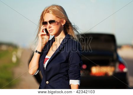 Young blond woman with broken car calling for help