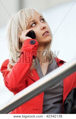 Young woman calling on the phone against office windows