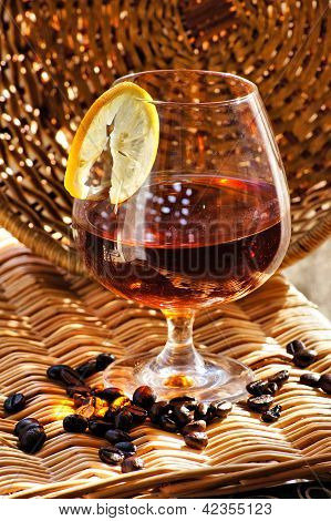 Glass Of Cognac With Lemon And Coffee Beans