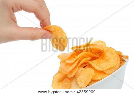 Hand with potato chips and bowl