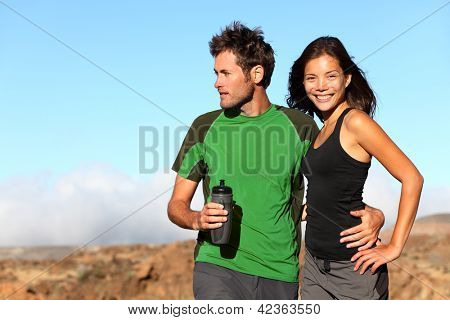 Young multicultural couple outdoors in sporty outfit. Portrait after running workout outside in mountains. Asian sport fitness woman and Caucasian man models.