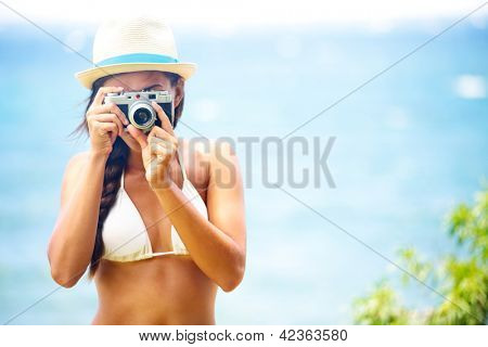 Summer beach woman holding vintage retro camera taking pictures looking at camera during summer holiday vacation travel at the ocean.