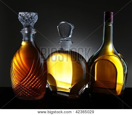 Three whiskey decanters against a light to dark gray background.