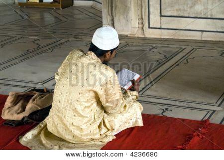 A Pious Devotee Reading The Quran Inside The Jama Masjid In Delhi