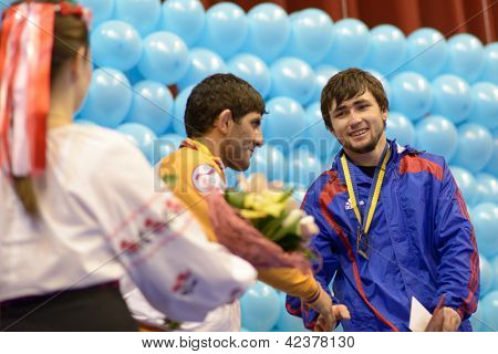 KIEV, UKRAINE - FEBRUARY 16: Mashezov, Russia (right) and Jaburian, Armenia on the award ceremony during XIX International freestyle wrestling tournament in Kiev, Ukraine on February 16, 2013