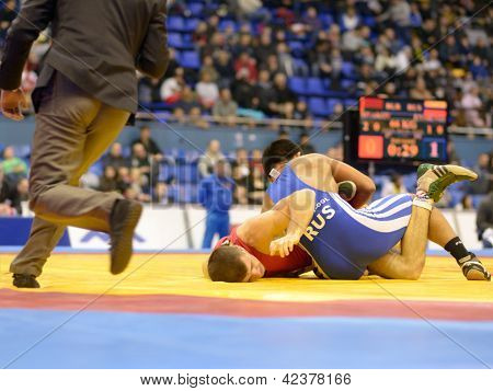 KIEV, UKRAINE - FEBRUARY 16: Match between Enmengi, Russia, blue and Sivakov, Belarus during XIX International freestyle wrestling and female wrestling tournament in Kiev, Ukraine on February 16, 2013