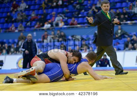 KIEV, UKRAINE - FEBRUARY 16: Final match between Istvan Vereb, Hungary, blue and Musa Murtazaliyev, Armenia during International freestyle wrestling tournament in Kiev, Ukraine on February 16, 2013