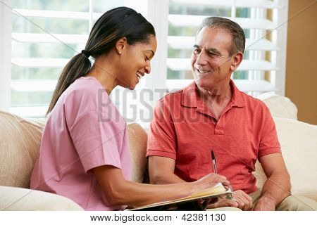 Nurse Discussing Records With Senior Male Patient During Home Visit