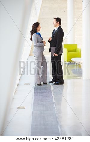 Businessman And Businesswomen Talking In Modern Office