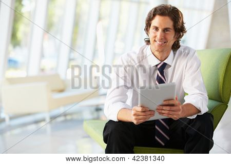 Businessman Sitting On Sofa In Office Using Digital Tablet