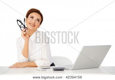 Beautiful businesswoman sitting at her desk with her glasses in her hand dayreaming with a lovely smile on her face as she stares up at the ceiling