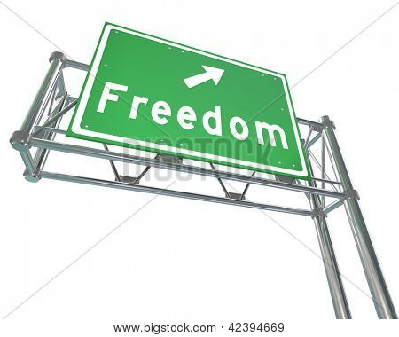 A green freeway sign with the word Freedom and an arrow pointing the way to a path of independence, liberty and autonomy